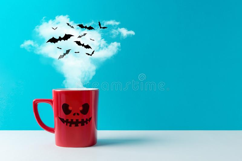 Halloween celebration concept with cup of coffee or hot drinks and bats on white table. Minimal holiday concept royalty free stock photos