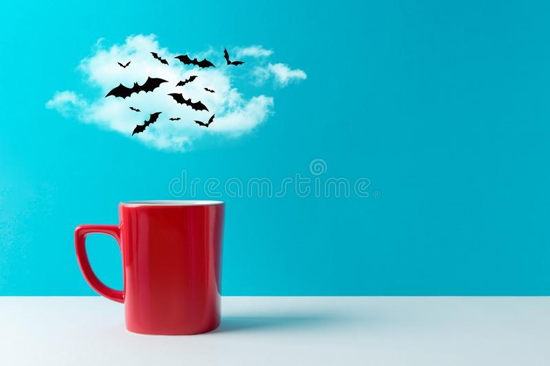 Halloween celebration concept with cup of coffee or hot drinks and bats on white table. stock photography