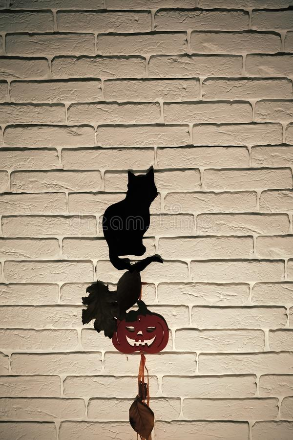 Halloween celebration concept. Black cat and orange pumpkin with tree leaves silhouettes paper cutouts on grey brick wall. Animal totem and holiday symbols royalty free stock image