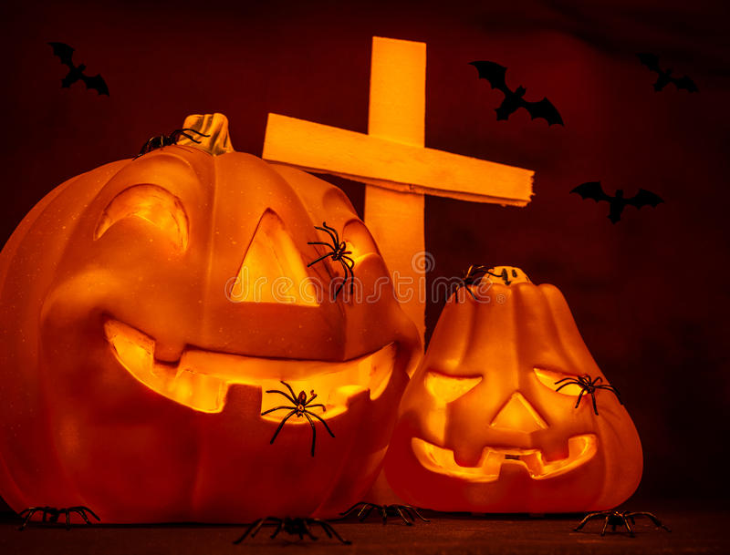 Halloween on cemetery. Glowing scary gourd and creepy cross, flying bats, mysterious night, autumn seasonal holiday of horror stock photo