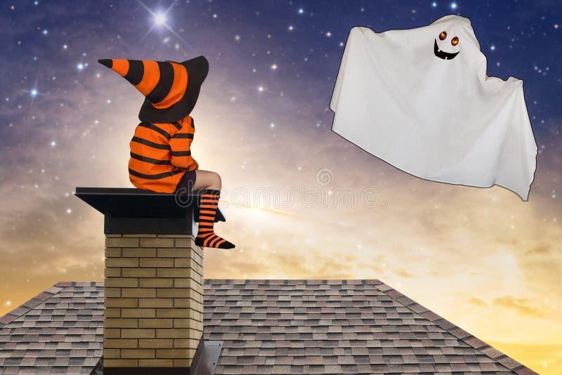 halloween Chłopiec siedzi na dachu w Halloweenowych kostiumach i patrzeje up przy latającym duchem obraz stock