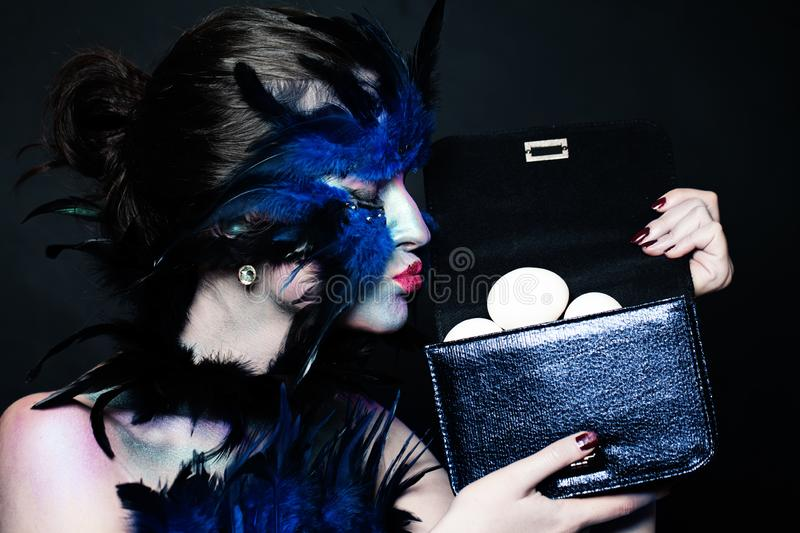 Halloween character, creative portrait. Model woman with bird makeup, feathers and eggs royalty free stock photo