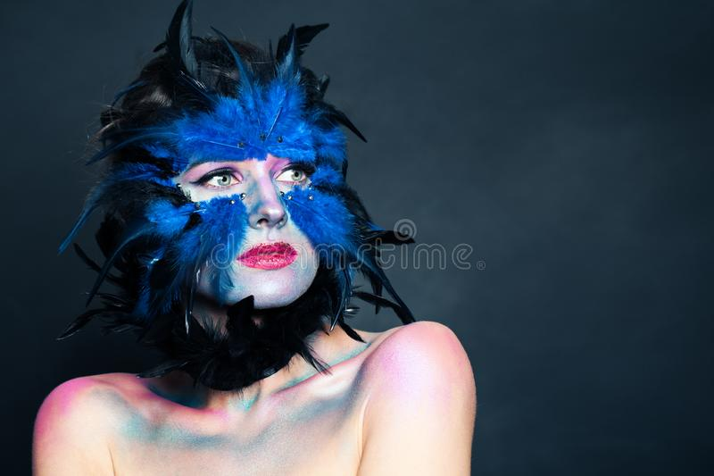 Halloween character portrait. Woman with creative blue bird makeup on dark background.  royalty free stock photos