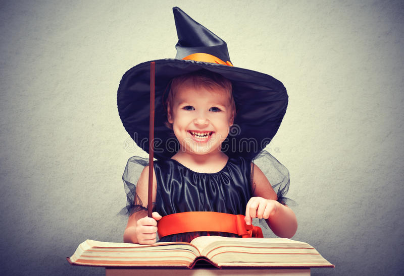 Halloween. cheerful little witch with magic wand and book conjur royalty free stock photos