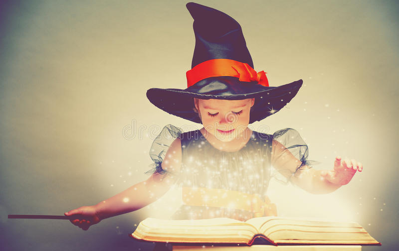 Halloween. cheerful little witch with a magic wand and glowing b royalty free stock photo