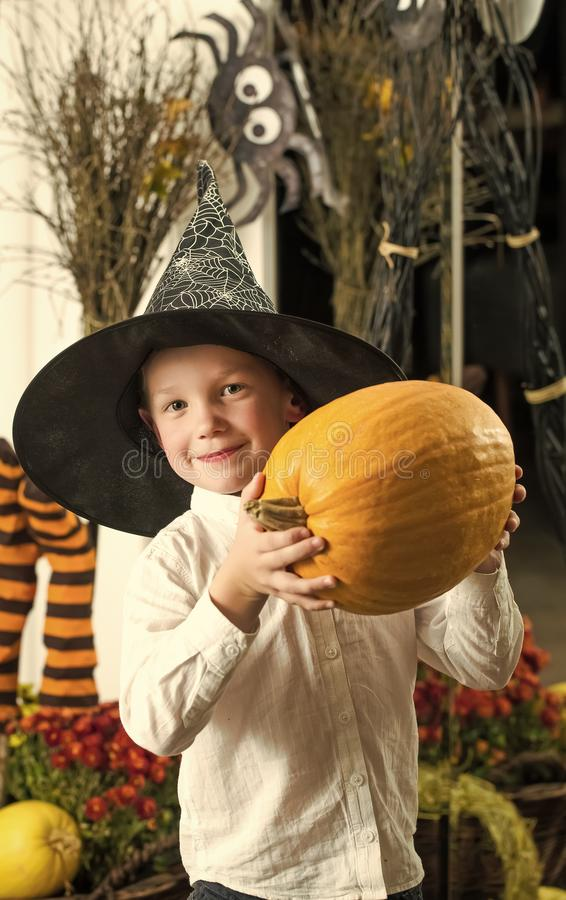 Halloween child with happy face. Kid with orange pumpkin in witch hat. Holiday and celebration. Small boy in spider web hat at striped socks. Party and stock image