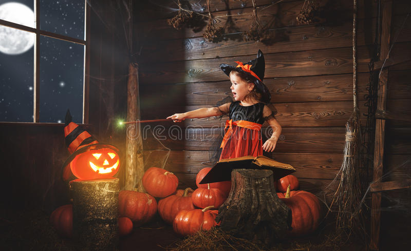 Halloween. child little witch with magic wand, pumpkin Jack mag royalty free stock photos
