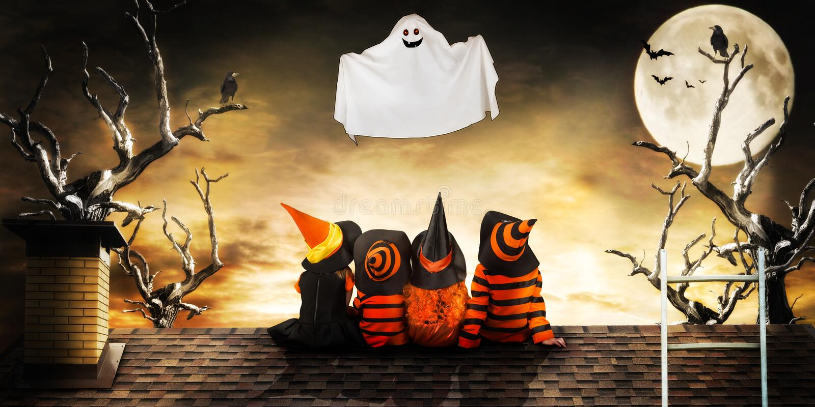 Halloween.Children in costumes of witches and wizard at night sit on the roof look at the flying ghost. stock images