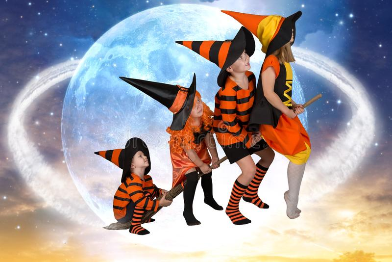 Halloween.The children of witches and wizards fly on broomsticks across the sky.Beautiful children in Halloween costumes. stock photo