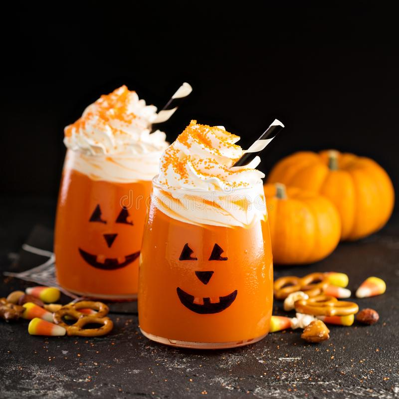Halloween cold cocktail or drink with jack o`lantern face. Halloween cold pumpkin cocktail or drink with jack o`lantern face and whipped cream royalty free stock photos