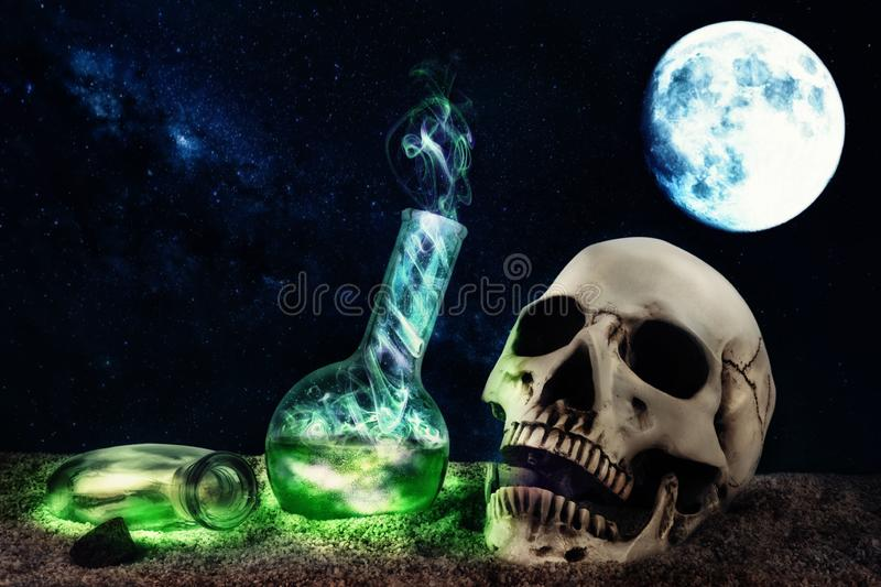 Halloween composition in desert scene with skull and mysterious smoking bottles. stock images