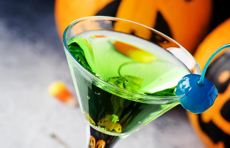 Halloween composition with festive drink, green cocktail and pumpkins lanterns, smoke and fallen leaves on night dark blue. Background, selective focus royalty free stock images