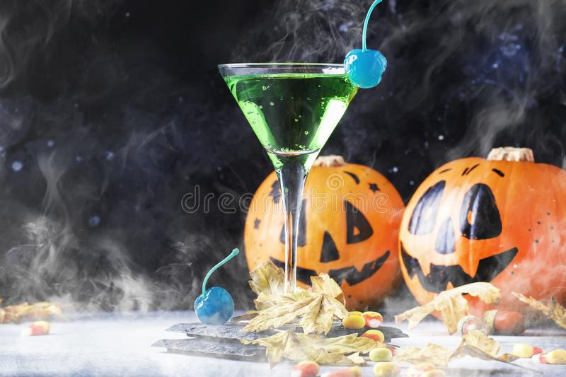 Halloween composition with festive drink, green cocktail and pumpkins lanterns, smoke and fallen leaves on night dark blue. Background, selective focus royalty free stock photography
