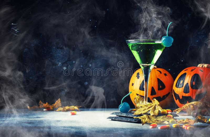 Halloween composition with festive drink, green cocktail and pumpkins lanterns, smoke and fallen leaves on night dark blue stock photos