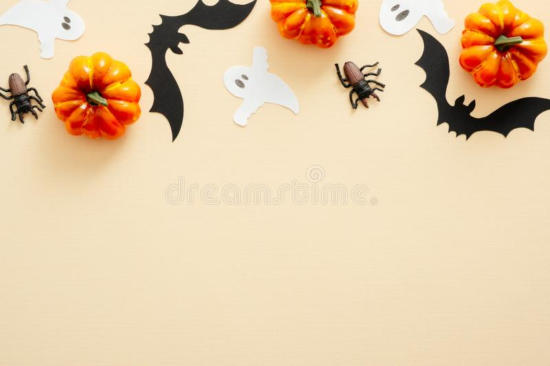 Halloween composition. Halloween decorations, pumpkins, paper ghost, spiders on pastel beige background. Halloween concept. Flat stock photo