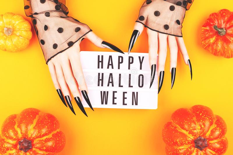 Halloween composition with witch hands holding a pumpkin royalty free stock photos