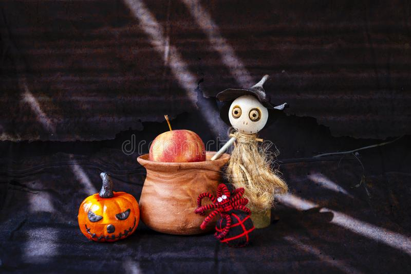 Cut little wooden witch doll making poison apple with her spider friend stock image
