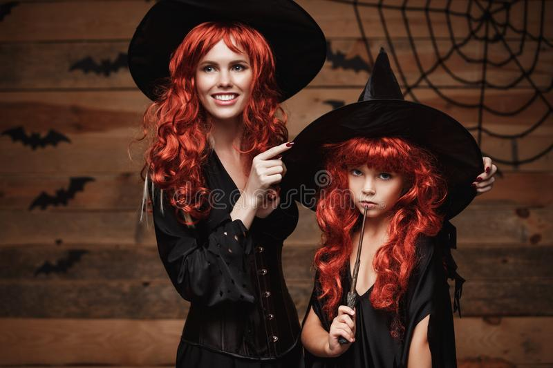 Halloween Concept - Beautiful caucasian mother dress up for her daughter in witch costumes and long curly hair ready for celebrati stock image
