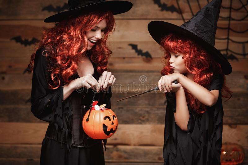 Halloween Concept - Beautiful caucasian mother and her daughter with long red hair in witch costumes with Halloween candy and magi stock photo