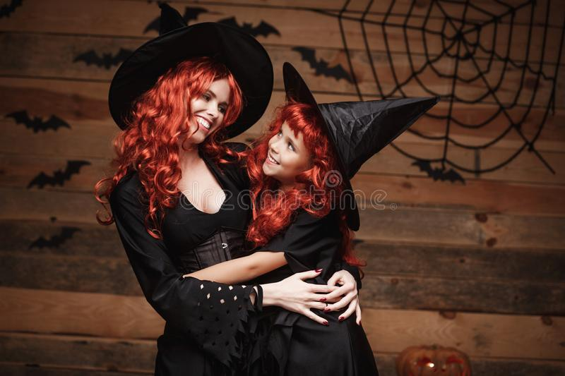 Halloween Concept - Beautiful caucasian mother and her daughter with long red hair in witch costumes happy smiling and hug each ot royalty free stock photography