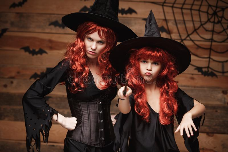 Halloween Concept - Beautiful caucasian mother and her daughter with long red hair in witch costumes and magic wand celebrating Ha. Lloween posing with over bats royalty free stock photo