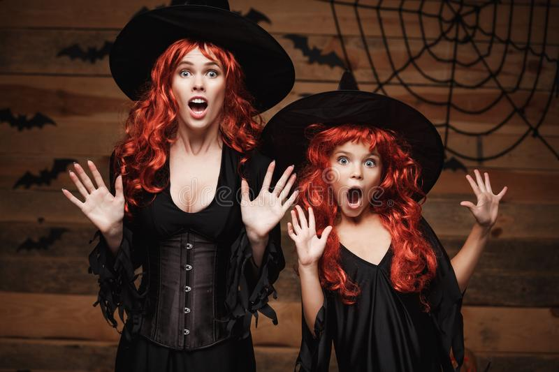 Halloween Concept - Beautiful caucasian mother and her daughter with long red hair in witch costumes with shocked facial expressio stock images