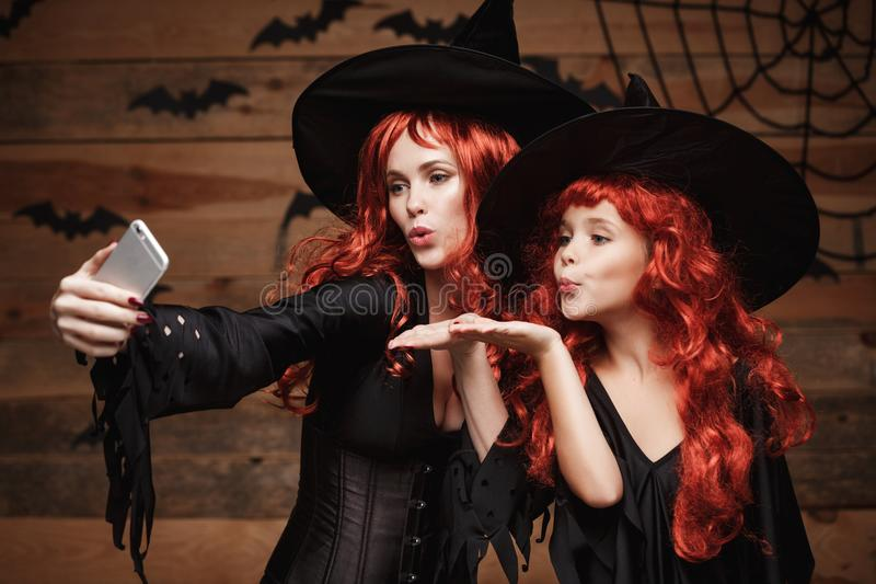 Halloween Concept - Beautiful caucasian mother and her daughter with long red hair in witch costumes taking a selfie. With smartphone ready for celebrating royalty free stock photos