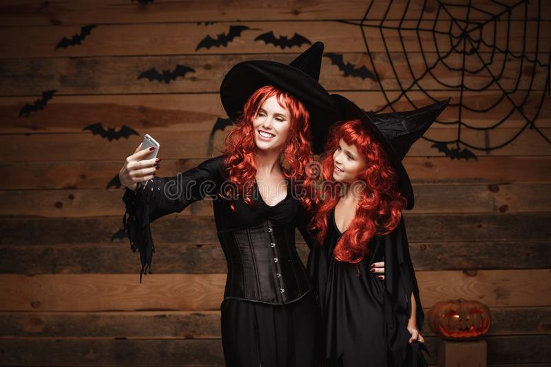 Halloween Concept - Beautiful caucasian mother and her daughter with long red hair in witch costumes taking a selfie with smartpho stock image
