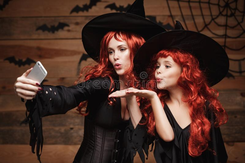 Halloween Concept - Beautiful caucasian mother and her daughter with long red hair in witch costumes taking a selfie with smartpho stock photos