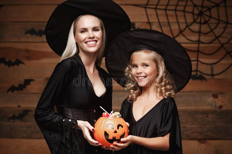 Halloween Concept - beautiful caucasian mother and her daughter in witch costumes celebrating Halloween with sharing Halloween can. Dy and sweet over bats and stock photos