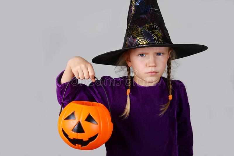 Halloween Concept. Beautiful child girl in witch costume with with pumpkin Jack. royalty free stock photography