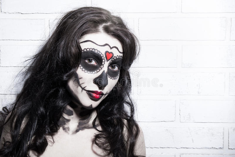 Halloween concept - beautiful woman with creative sugar skull ma. Halloween concept - portrait of beautiful woman with creative sugar skull make up over white royalty free stock images