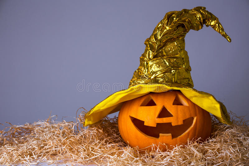 Halloween concept - big pumpkin Jack-O-Lantern in witch hat over stock photos