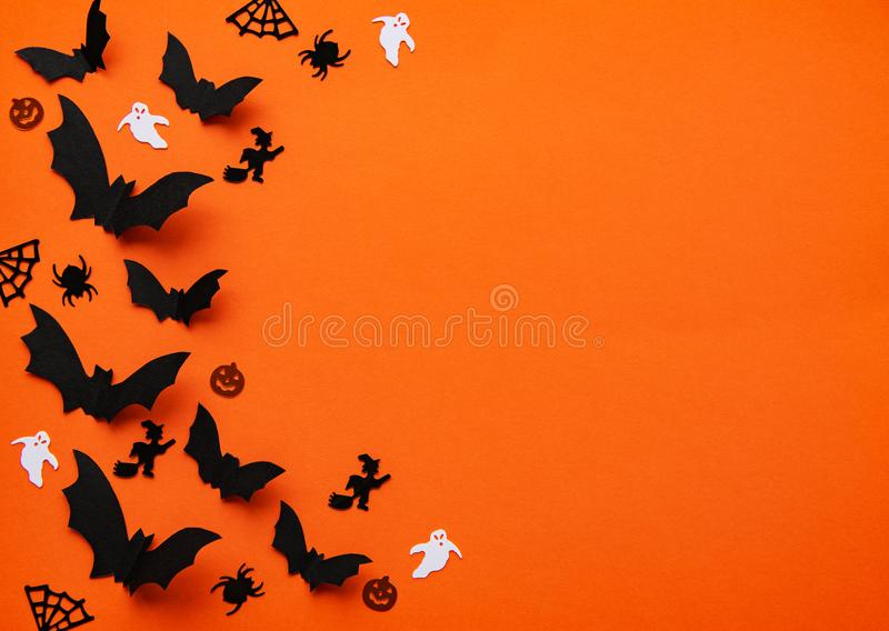 Halloween holiday decorations. Halloween  concept - black paper bats and decorations flying over orange background stock images