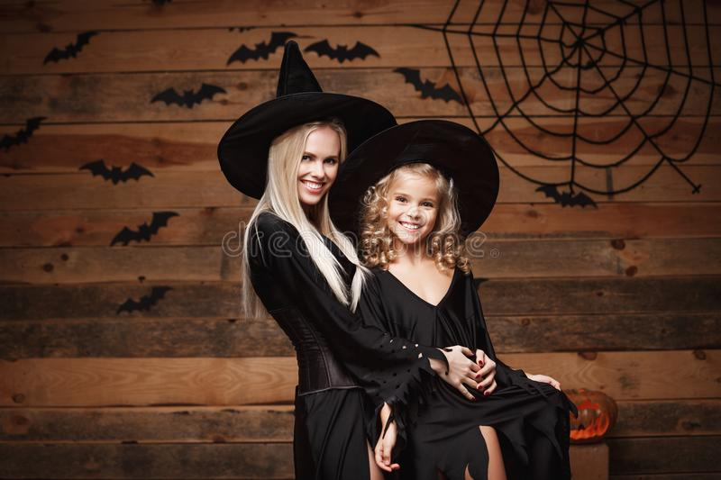 Halloween Concept - cheerful mother and her daughter in witch costumes celebrating Halloween posing with curved pumpkins over bats. And spider web on Wooden royalty free stock photos