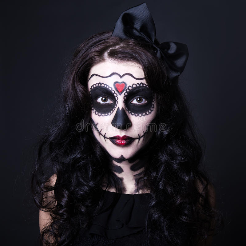 Halloween concept - close up of young woman with skull make up stock image