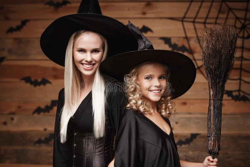 Halloween Concept - Closeup beautiful caucasian mother and her daughter in witch costumes celebrating Halloween posing with curved royalty free stock images