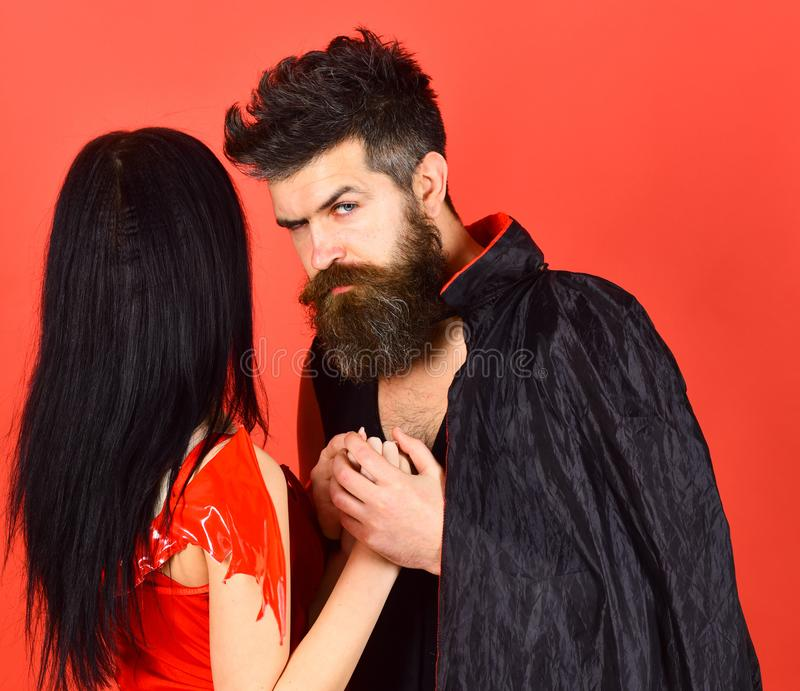 Halloween concept. Couple on pensive faces play role game. Vampire in cloak and devil girl holds hands. Couple in. Love, perfect match. Man and women dressed stock image