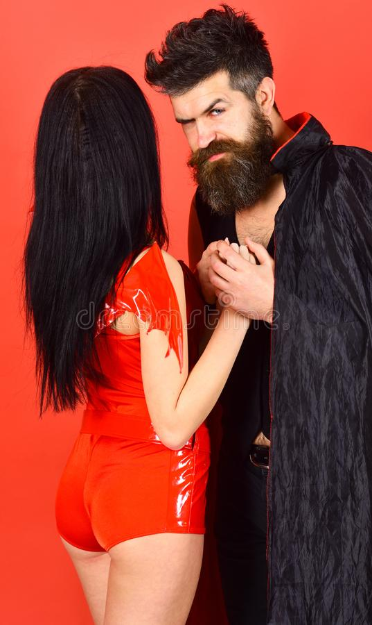 Halloween concept. Couple on strict face play role game. Vampire in cloak and devil girl holds hands. Couple in. Love, perfect match. Man and women dressed like royalty free stock photo