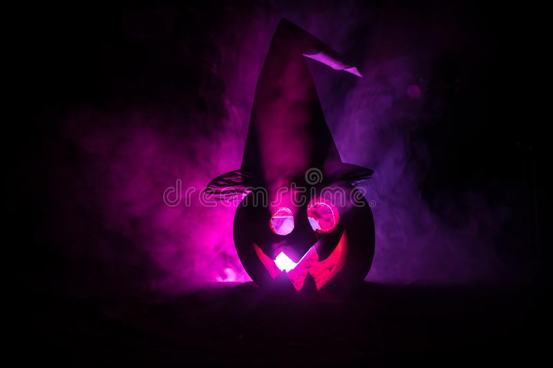 Halloween concept. Jack-o-lantern smile and scary eyes for party night. Close up view of scary pumpkin with witch hat on at dark f stock images