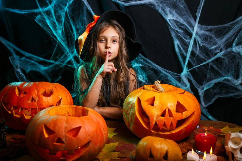 Happy Halloween . Little girl in witch costume celebrating Halloween doing silence gesture posing with curved pumpkins stock photo