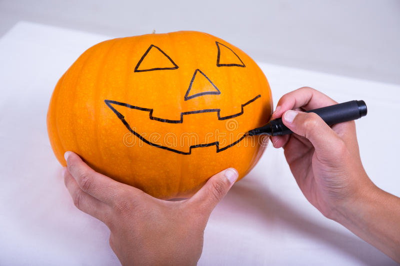 Halloween concept - male hands drawing pumpkin with marker stock photo