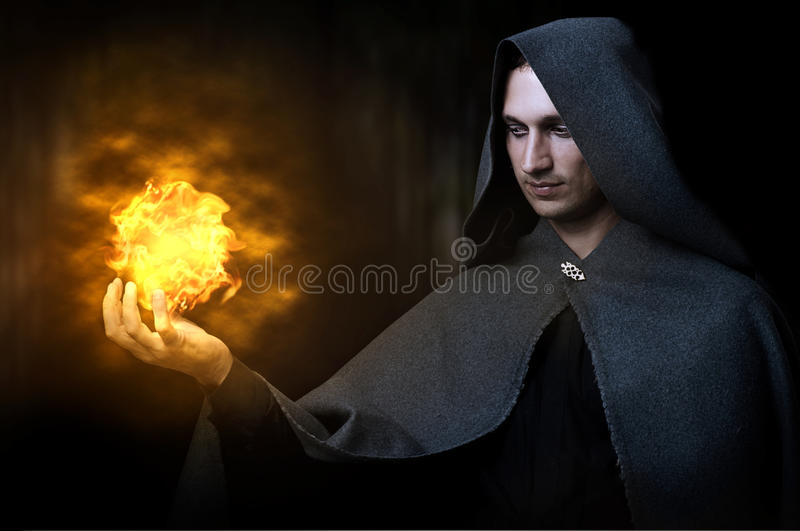 Halloween concept. Male wizard with fireball. Halloween concept. Powerful Male witch or wizard with fireball in hands. Ball from fire burns stock image