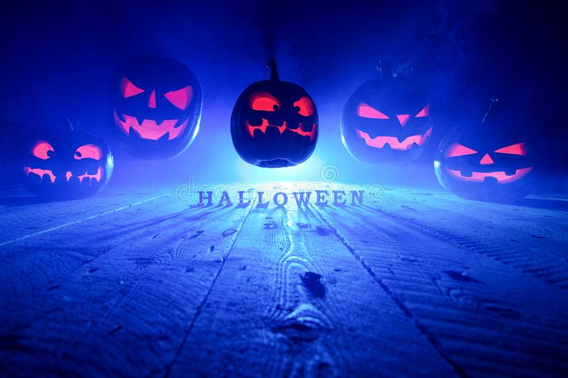 Halloween concept. Many glowing fiery light angry scary pumpkins. Flying through the air. Jack Lantern, with Halloween inscription, with a blue cool light stock image