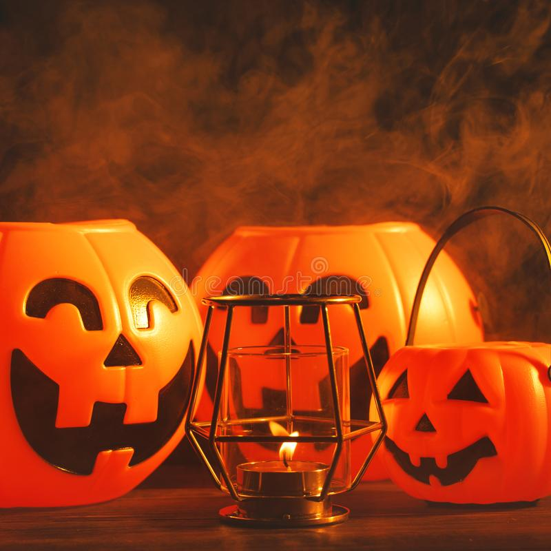 Halloween concept - Orange plastic pumpkin lantern with laugh face on a dark wooden table with smoke around the background, trick royalty free stock image