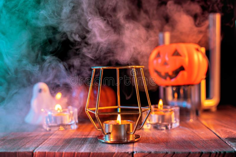 Halloween concept, orange pumpkin lantern and candles on a dark wooden table with green-orange smoke around the background, trick royalty free stock photo