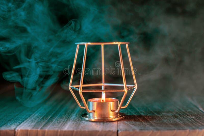 Halloween concept, orange pumpkin lantern and candles on a dark wooden table with green-orange smoke around the background, trick stock photos