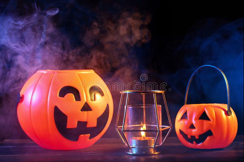 Halloween concept - Orange pumpkin lantern on a dark wooden table with double colored smoke around the background, trick or treat. Close up stock images