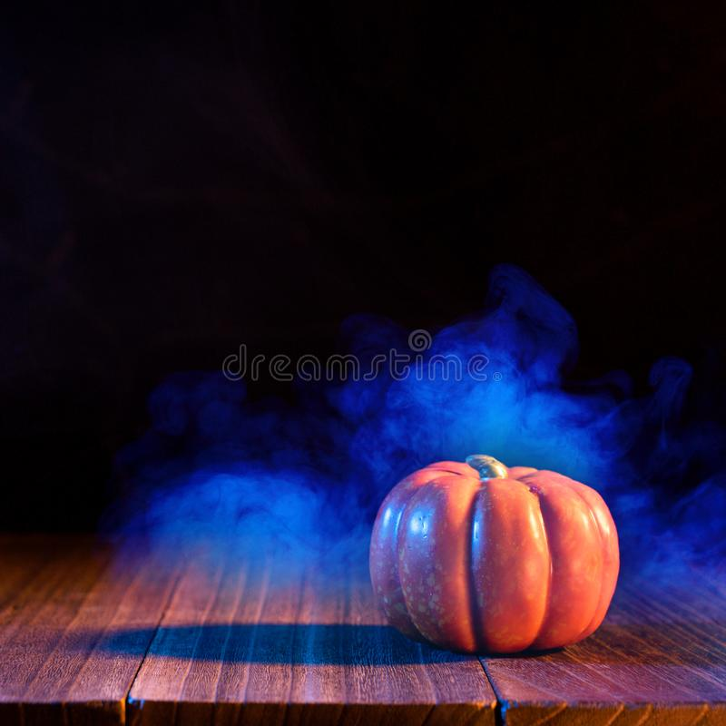 Halloween concept - Orange pumpkin lantern on a dark wooden table with double colored smoke around the background, trick or treat. Close up royalty free stock images