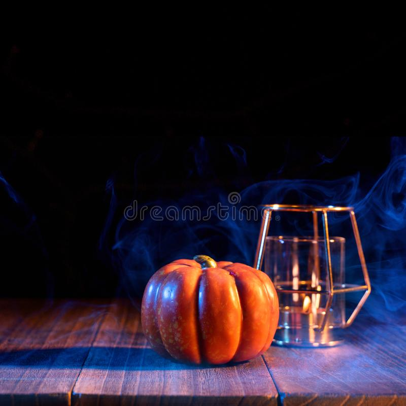 Halloween concept - Orange pumpkin lantern on a dark wooden table with double colored smoke around the background, trick or treat. Close up stock photography